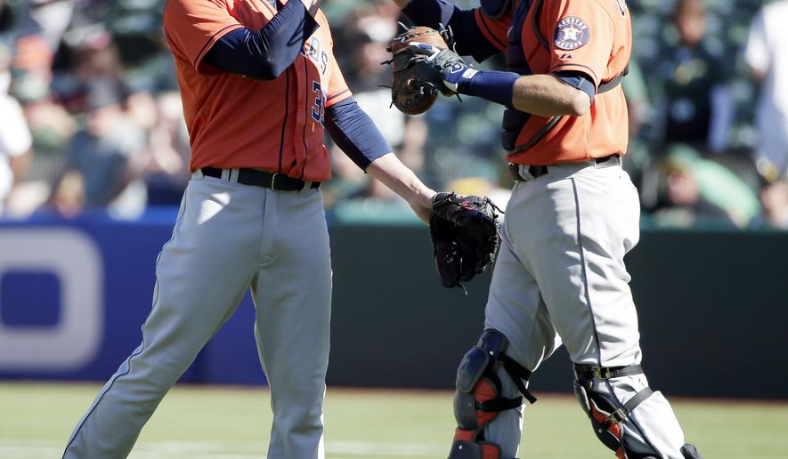 Houston Astros relief pitcher Josh Fields, left, celebrates with catcher Jason Castro after the last out of the game in a 5-3 win over the Oakland Athletics during the ninth inning of a baseball game on Sunday, Sept. 7, 2014, in Oakland, Calif. (AP Photo/Marcio Jose Sanchez)