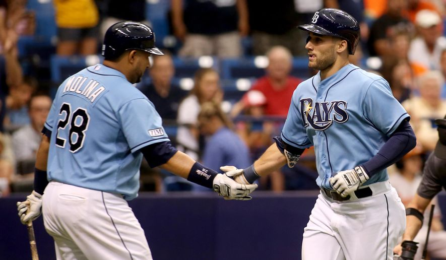 Tampa Bay Rays right fielder Kevin Kiermaier, right, gets a handshake from teammate Jose Molina (28) after crossing the plate following a solo home run during the sixth inning of a baseball game against the Baltimore Orioles, Sunday, Sept. 7, 2014, in St. Petersburg, Fla.. (AP Photo/Reinhold Matay)