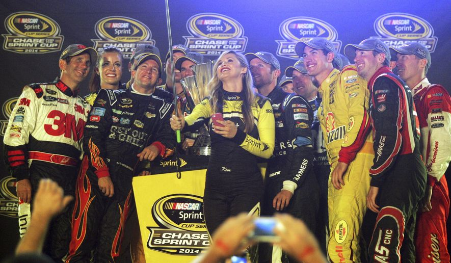 Chase for the Sprint Cup drivers pose for a photo with Miss Sprint Cup after the NASCAR race at Richmond International Raceway in Richmond, Va., early Sunday, Sept. 7, 2014. (AP Photo/Jason Hirschfeld)