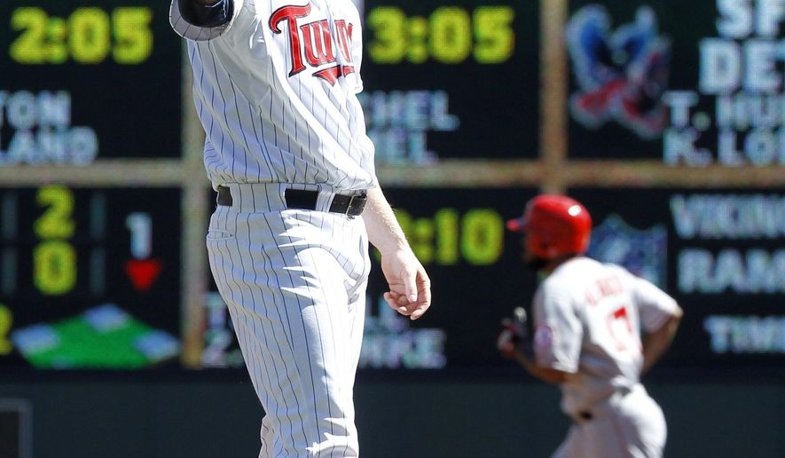 Minnesota Twins starting pitcher Logan Darnell waits for a new ball as Los Angeles Angels' Howie Kendrick, background right, rounds the bases on a solo home run during the second inning of a baseball game in Minneapolis, Sunday, Sept. 7, 2014. (AP Photo/Ann Heisenfelt)