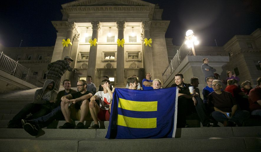 Same-sex marriage supporters gather on the steps of the Idaho Statehouse in Boise after U.S. Magistrate Judge Candy Dale ruled earlier in the day that Idaho's ban on gay marriage is unconstitutional in this May 13, 2014, file photo. (AP Photo/The Idaho Statesman, Kyle Green, File)