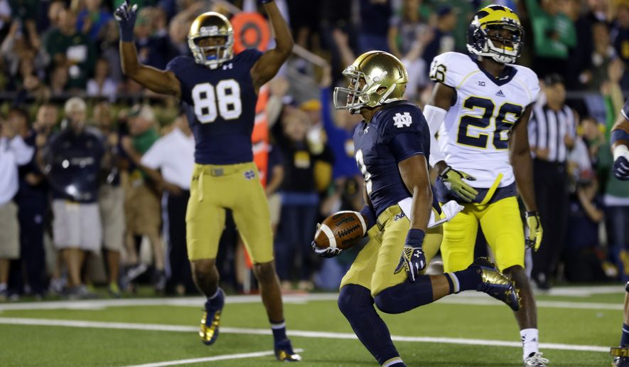 Notre Dame wide receiver Amir Carlisle runs in for a touchdown in front of teammates wide receiver Corey Robinson and Michigan defensive back Jourdan Lewis during the second half of an NCAA college football game in South Bend, Ind., Saturday, Sept. 6, 2014. (AP Photo/Michael Conroy)