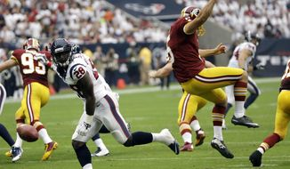 Houston Texans' Alfred Blue (28) blocks a punt by Washington Redskins' Tress Way (5) during the second quarter of an NFL football game Sunday, Sept. 7, 2014, in Houston. Blue scored on the play. (AP Photo/David J. Phillip)