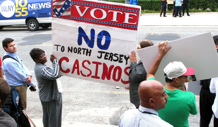 Protestors hold signs across the street from a meeting New Jersey Gov. Chris Christie convened on Monday Sept. 8, 2014 on the future of Atlantic City. The meeting came hours after Christie's administration said it will allow the state's casinos and horse tracks to offer sports betting, a move certain to be challenged in court by the professional and collegiate sports leagues. (AP Photo/Wayne Parry)