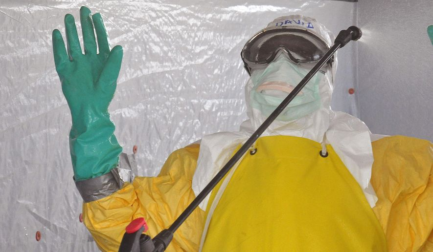 A health worker is sprayed with disinfectant after he worked with patients that contracted the Ebola virus, at a clinic  in Monrovia, Liberia, Monday, Sept. 8, 2014.  Border closures, flight bans and mass quarantines are creating a sense of siege in the West African countries affected by Ebola, officials at an emergency African Union meeting said Monday, as Senegal agreed to allow humanitarian aid pass through its closed borders. (AP Photo/Abbas Dulleh)