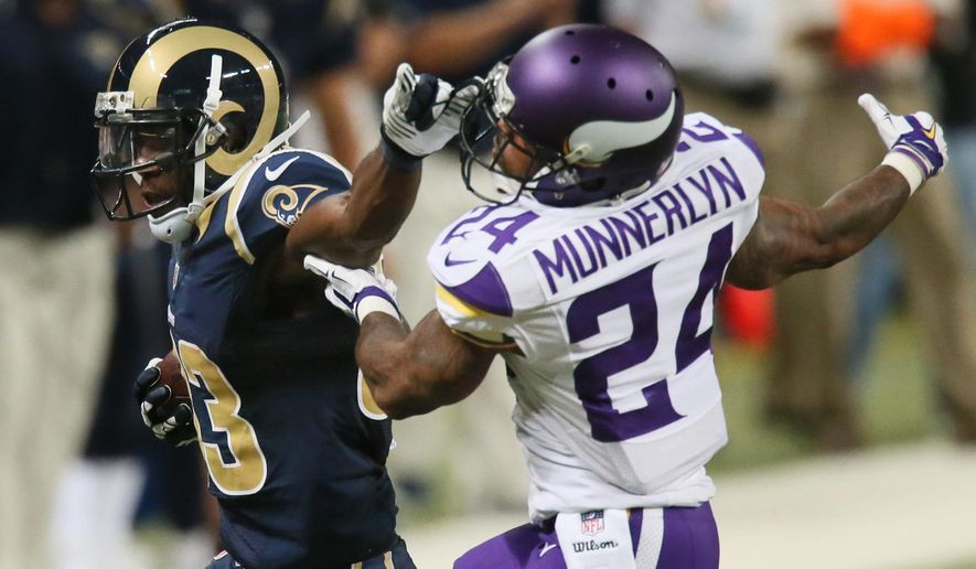 St. Louis Rams wide receiver Brian Quick hooks the facemask of Minnesota cornerback Captain Munnerlyn as he gains 21 yards on a reception in second quarter action during a game between the St. Louis Rams and Minnesota Vikings on Sunday, Sept. 7, 2014, at the Edward Jones Dome in St. Louis.  A facemask penalty on Quick reduced the gain to six yards.   (AP Photo/St. Louis Post-Dispatch, Chris Lee)  EDWARDSVILLE INTELLIGENCER OUT; THE ALTON TELEGRAPH OUT