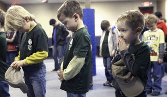 """Young members of Trail Life USA pause for prayer during a meeting in Texas. The mission of the organization, created as an alternative to the Boy Scouts of America, is to help """"the boy of today become the man of tomorrow,"""" group leaders said. (Associated Press)"""