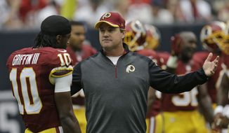 FILE - In this Sept. 7, 2014, file photo, Washington Redskins head coach Jay Gruden talks to quarterback Robert Griffin III  before an NFL football game against the Houston Texans in Houston. Game 1 of the Jay Gruden era with the  Redskins looked a lot like the final games under Mike Shanahan. (AP Photo/David J. Phillip, File)