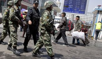 Armed Chinese paramilitary policemen march past the site of the explosion outside the Urumqi South Railway Station in Urumqi in northwest China's Xinjiang Uygur Autonomous Region in this Thursday, May 1, 2014, file photo. (AP Photo/Ng Han Guan, File)