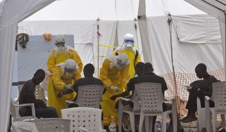 ** FILE ** Health workers, attend to patients that contracted the Ebola virus, at a clinic  in Monrovia, Liberia, Monday, Sept. 8, 2014. (AP Photo/Abbas Dulleh)