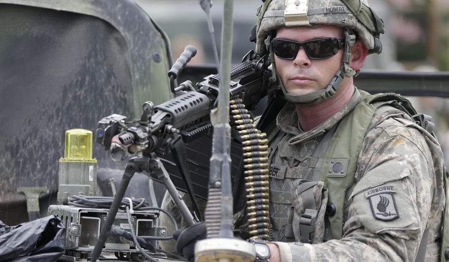 """A US soldier takes part in an exercise called """"Saber Junction"""" at the military area in Hohenfels near Regensburg, southern Germany, Monday, Sept. 8, 2014. Saber Junction 14 is a U.S. Army Europe led, U.S. European Command directed, multinational, multiservice exercise that involves more than 5,800 personnel from 17 European countries. (AP Photo/Matthias Schrader)"""