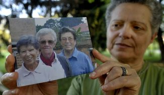 """Silvia Marsili, an official of Saverian missionaries' head convent in Parma, Italy, shows a photo of the three Italian missionary nuns, from left, Bernardetta Boggian, Olga Raschietti and Lucia Pulici,  found slain in their convent in Burundi, Monday, Sept. 8, 2014. The Italian foreign ministry confirmed the slayings in Kamenge, near Bujumbura, Burundi's capital. Pope Francis, in a condolence telegram to Bujumbura's archbishop, said he """"learned with great sadness of the murder"""" of the three """"faithful and devout nuns in these tragic circumstances."""" (AP Photo/Marco Vasini)."""