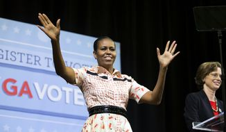 First lady Michelle Obama, left, takes the stage during a voter registration rally with Democratic U.S. Senate candidate Michelle Nunn, right, Monday, Sept. 8, 2014, in Atlanta. (AP Photo/David Goldman)