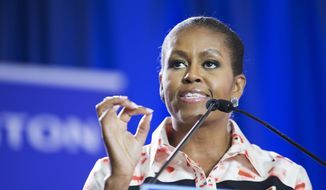 ** FILE ** First lady Michelle Obama speaks at Booker T. Washington High School in Atlanta, Monday, Sept. 8, 2014, as part of her Reach Higher educational initiative. (AP Photo/David Goldman)