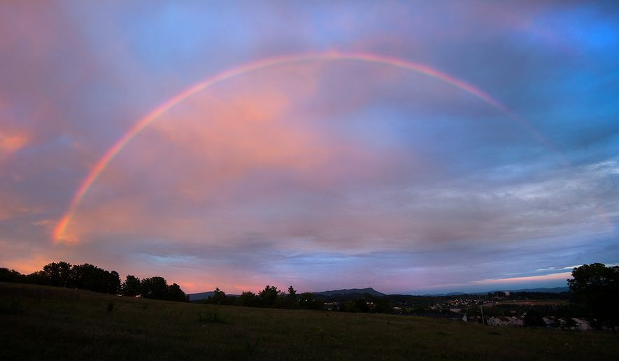 Water droplets in low clouds and the angle of the setting sun form the right conditions for a double rainbow over Harrisonburg, Va., and the distant Massanutten Peak looking east from Pear Street Sunday evening, Sept. 7, 2014.   (AP Photo/Daily News-Record, Michael Reilly)