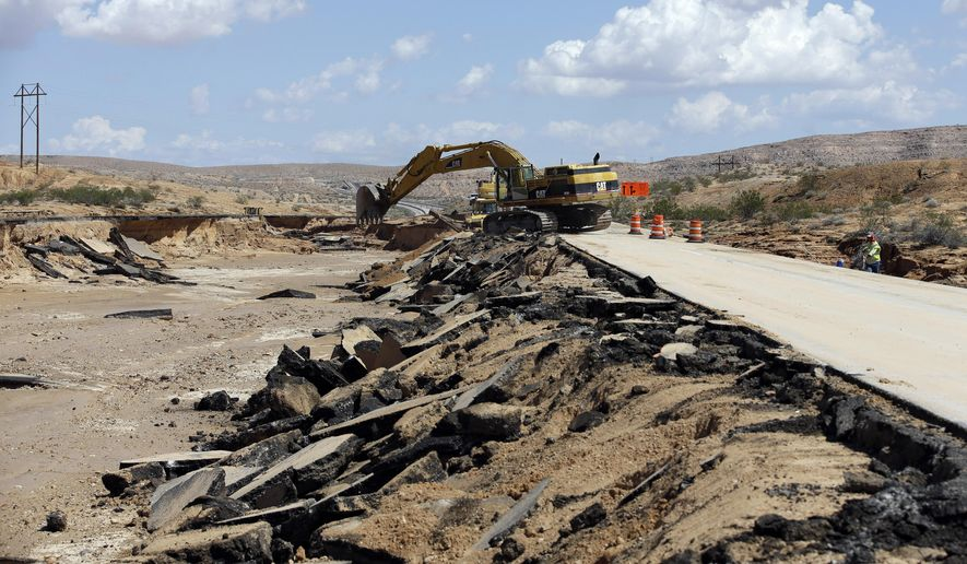 Construction crews work on a flood damaged area of Interstate 15 Tuesday, Sept. 9, 2014, near Moapa, Nev. Flood damage caused the closure of the interstate which is the main road between Las Vegas and Salt Lake City. (AP Photo/John Locher)