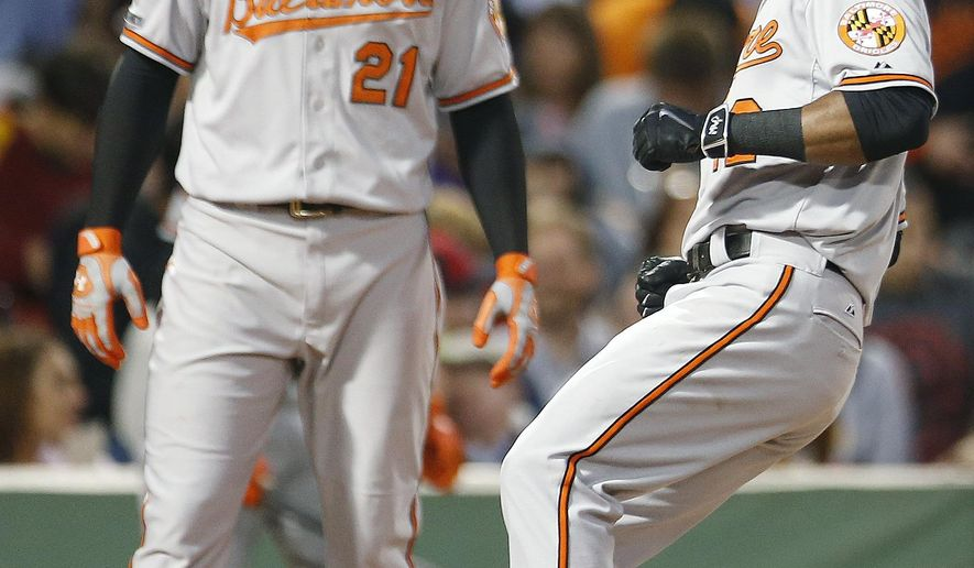 Baltimore Orioles' Alejandro De Aza, right, touches home plate on his two-run home run that also drove in Nick Markakis (21) during the first inning of a baseball game against the Boston Red Sox in Boston, Tuesday, Sept. 9, 2014. (AP Photo/Michael Dwyer)