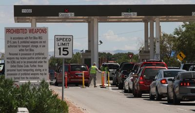 A soldier moves a traffic cone as cars wait to enter Fort Bliss in El Paso, Texas, Tuesday, Sept. 9,  2014. The Army is ramping up security at Fort Bliss, its sprawling West Texas post near the US-Mexico border. The tighter security is to include random vehicle checks and access limited to Defense Department personnel at some of its gates. (AP Photo/Juan Carlos Llorca)