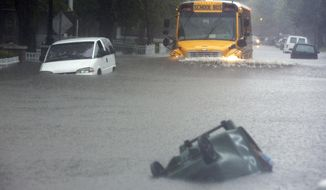 A school bus tries to go through a flooded Bagnall Road in Norfolk, Va., on Monday, Sept. 8, 2014 while a stalled vehicle sit on the side and a trash bin is floats down the street during a heavy rain. Gov. Terry McAuliffe will address the new Climate Change and Resiliency Commission on Wednesday, Sept. 10, when its 30-plus members meet in Richmond. (AP Photo/The Virginian-Pilot, The' N. Pham)