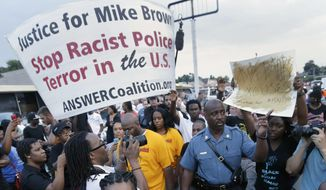 FILE - In this Aug, 16, 2014 file photo, Missouri Highway Patrol Capt. Ron Johnson walks among people protesting the police shooting death of Michael Brown a week ago in Ferguson, Mo. The Ferguson City Council, set to meet Tuesday, Sept. 9, 2014, for the first time since the fatal shooting of Brown, said it plans to establish a review board to help guide the police department and make other changes aimed at improving community relations. (AP Photo/Charlie Riedel, File)