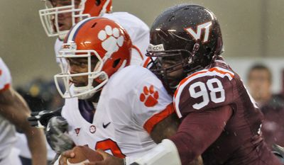 Clemson quarterback Tajh Boyd ,left, is sacked by Virginia Tech defensive tackle Derrick Hopkins (98) during the first half of an NCAA college football game at Lane Stadium in Blacksburg, Va., Saturday, Oct. 1, 2011. (AP Photo/Steve Helber)