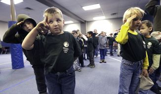 In this Tuesday, Feb. 4, 2014 photo, Trail Life member Adrian McCade, 7, second from left, gets direction on hand placement for the salute from his older brother Jack McCade, 8, during a group meeting in North Richland Hills, Texas. John Stemberger, an Orlando, Fla. lawyer who led the opposition to the Boy Scouts of America's May 2013 vote to accept openly gay youth, went on to found Trail Life. (AP Photo/LM Otero)