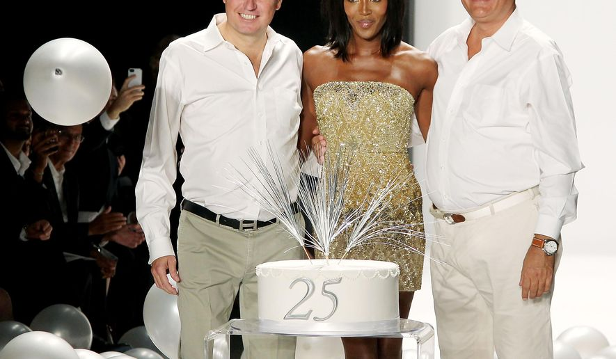 In this image released by Starpix, model Naomi Campbell, center poses with designers James Mischka, left, and Mark Badgley to celebrate their 25th Anniversary after the Badgley Mischka Spring 2015 collection was modeled during Fashion Week in New York on Tuesday, Sept. 9, 2014. (AP PHoto/Starpix, Marion Curtis)