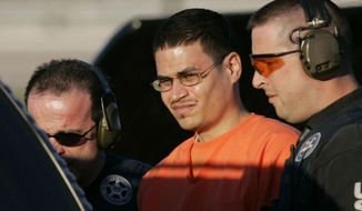 "FILE - In this Jan. 5, 2006 file photo, Jose Padilla, center, is escorted to a waiting police vehicle by federal marshals near downtown Miami. Padilla is set to be sentenced a second time by a federal judge Tuesday, Sept. 9, 2014 in Miami, because the original prison term of 17 years was too lenient. Padilla was arrested by the FBI in 2002 on what authorities said was an al-Qaida mission to detonate a radioactive ""dirty bomb"" inside the U.S. Those accusations were later discarded. (AP Photo/J. Pat Carter, File)"