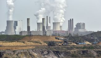 FILE - In this April 3, 2014 file photo giant machines dig for brown coal at the open-cast mining Garzweiler in front of a smoking power plant near the city of Grevenbroich in western Germany.  The U.N. weather agency says carbon dioxide levels in the atmosphere reached a record high in 2013. The World Meteorological Organization says the heat-trapping gas blamed for global warming was at global concentrations of 396 parts per million last year. That is an increase of 2.9 ppm from the previous year, which the Geneva-based agency reported Tuesday, Sept. 9, 2014 was the biggest year-to-year change in three decades. (AP Photo/Martin Meissner, File)