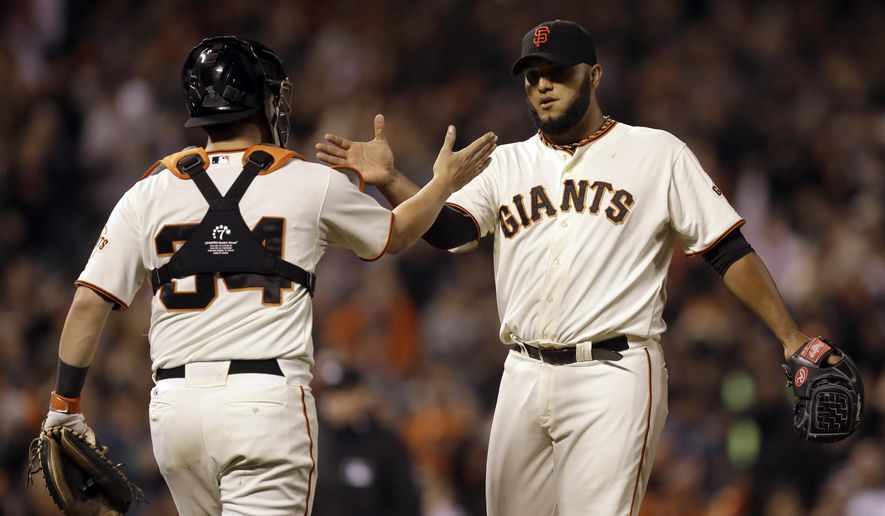 San Francisco Giants' Yusmeiro Petit, right, and Andrew Susac celebrate the Giants' 5-1 defeat of the Arizona Diamondbacks in baseball game Tuesday, Sept. 9, 2014, in San Francisco. (AP Photo/Ben Margot)