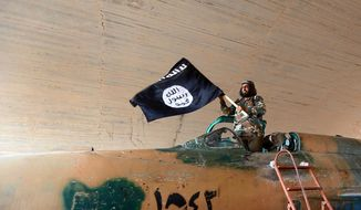 This undated file image posted on Aug. 27, 2014, by the Raqqa Media Center of the Islamic State group, a Syrian opposition group, shows a fighter of the Islamic State group waving their flag from inside a captured government fighter jet following the battle for the Tabqa air base, in Raqqa. The image has been verified and is consistent with other AP reporting. (AP Photo/Raqqa Media Center of the Islamic State group, File)