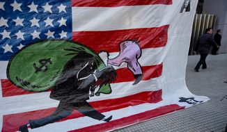 A banner shows a vulture, symbolizing a U.S. hedge fund, carrying a bag of money in front of the U.S. flag outside Congress in Buenos Aires, Argentina, Wednesday, Sept. 10, 2014. Congress is expected to vote on a bill, that if approved, would allow Argentina to pay creditors locally in Argentina. Argentina was forced into a second default on July 30 following a decade-long legal battle with U.S. investors including hedge funds who refused to accept lower payments for bonds that the South American country defaulted on in 2001. The investors obtained a U.S. court order, preventing Argentina from making interest payments which triggered the second default. (AP Photo/Natacha Pisarenko)