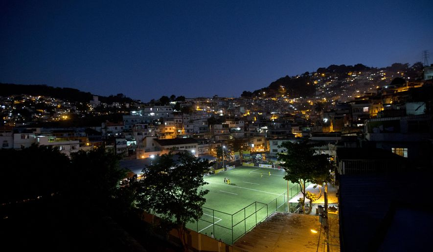 Residents of the Morro da Mineira favela play in the newly installed soccer pitch powered by player's footsteps, in Rio de Janeiro, Brazil, Wednesday, Sept. 10, 2014.  The project, sponsored by British oil giant Shell, has around 200 energy-capturing tiles installed along the width and breadth of the field and covered by a layer of AstroTurf. Working in conjunction with solar panels also installed around the field, the player-powered tiles feed electricity to a system of floodlights overhead. (AP Photo/Silvia Izquierdo)