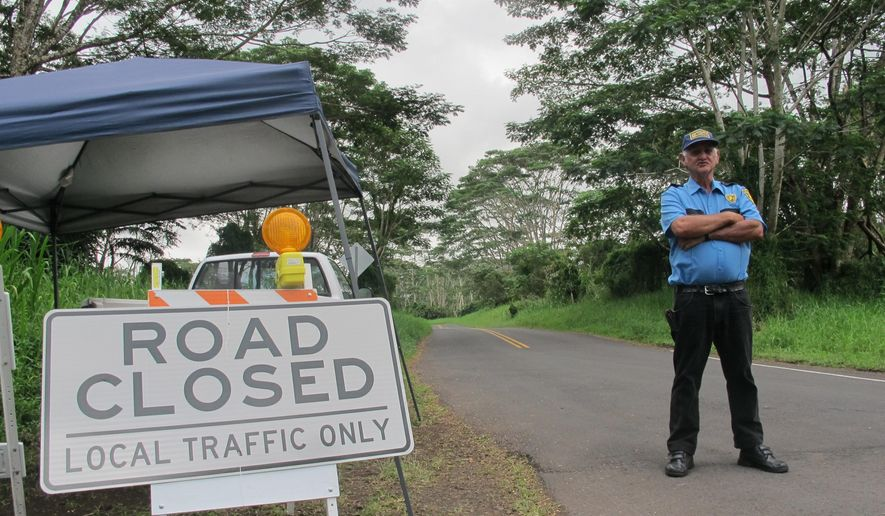 In this Monday, Sept. 8, 2014 photo, security guard George Cortez stands at a roadblock to prevent non-residents from entering the lava-threatened community of Kaohe Homesteads in Pahoa, Hawaii. Those who live on the slopes of Kilauea volcano know lava could start creeping their way at any time but the area is still a powerful draw for many people who value its community and affordability. (AP Photo/Audrey McAvoy)