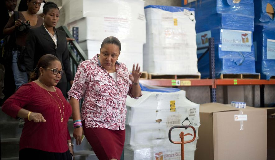 Haiti's Health Minister Florence Duperval Guillaume, left, leads a tour for first lady Sophia Martelly through a warehouse housing a donation of kits to treat chikungunya, in the Cite Soleil slum, in Port-au-Prince, Haiti, Wednesday, Sept. 10, 2014. The U.S. medical aid group Direct Relief donated millions of kits to treat the mosquito-borne virus that has sickened tens of thousands across the Caribbean over the past year. (AP Photo/Dieu Nalio Chery)