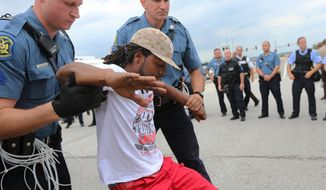 A man is arrested during a protest at Hanley Road and Interstate 70 during an attempt to shut down Interstate 70 in Berkeley, Mo. on Wednesday, Sept. 10, 2014 near the St. Louis suburb of Ferguson, Mo. where Michael Brown, an unarmed, black 18-year-old was shot and killed by a white police officer on Aug. 9. (AP Photo/St. Louis Post-Dispatch, David Carson)