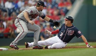 Washington Nationals' Asdrubal Cabrera (3) is safe at third against Atlanta Braves third baseman Chris Johnson, left, on a single by Danny Espinosa during the second inning of a baseball game, Wednesday, Sept. 10, 2014, in Washington. (AP Photo/Nick Wass)
