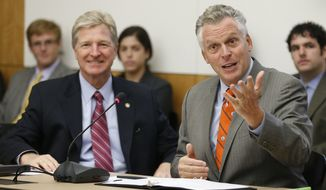 Virginia Gov. Terry McAuliffe, right, gestures as he addresses the Governor's Commission on Climate Change as Virginia Sec. of Public Safety, Brian Moran, left, looks on at the Capitol in Richmond, Va., Wednesday, Sept. 10, 2014. (AP Photo/Steve Helber)