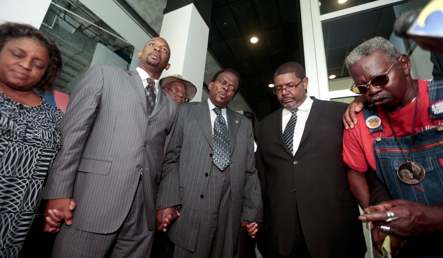 Civil rights leaders led by Rev. Markel Hutchins, second from left, pray in the lobby of the Phillips Arena after a scheduled meeting between Atlanta Hawks CEO Steve Koonin and Atlanta civil rights leaders was cancelled, Wednesday, Sept. 10, 2014, in Atlanta. (AP Photo/John Bazemore)