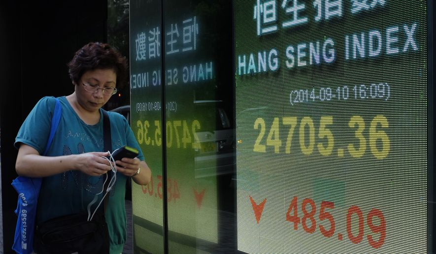 A woman walks past an electronic board of a local bank showing the Hong Kong share index in Hong Kong Wednesday, Sept. 10, 2014. Global stocks sank under the weight of worries about the possible timing of a U.S. rate hike, economic weakness in China and an impending referendum on Scottish independence. Hong Kong's Hang Seng fell 1.9 percent to 24,705.36. (AP Photo/Vincent Yu)