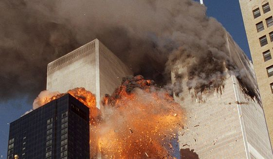 In this Sept. 11, 2001, file photo, smoke billows from World Trade Center Tower 1 and flames explode from Tower 2 as it is struck by United Airlines Flight 175, in New York. (AP Photo/Chao Soi Cheong, File)