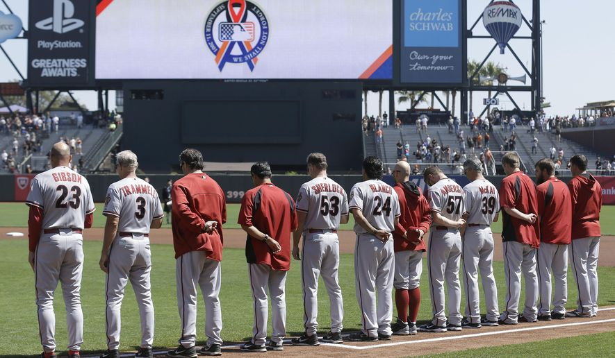 Arizona Diamondbacks players observe a moment of silence of 9/11 before a baseball game  against the San Francisco Giants in San Francisco, Thursday, Sept. 11, 2014. (AP Photo/Jeff Chiu)