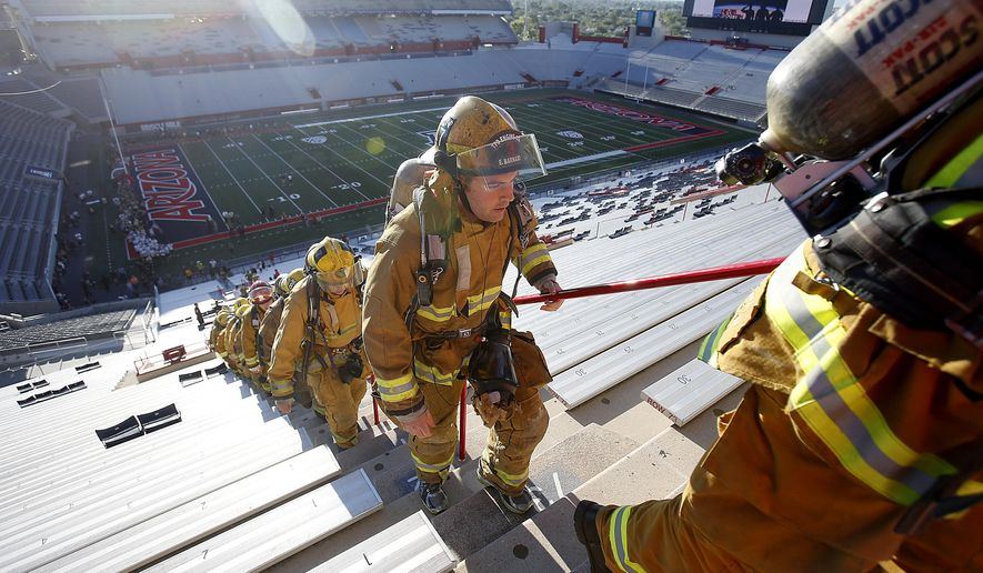 Firefighters from the Tucson Fire Department led over 300 law enforcement, firefighters, military personnel and residents in the first 9/11 Tower Challenge at University of Arizona Stadium early Thursday Sept. 11, 2014. Participants climbed 2,071 steps to memorialize the first responders who climbed stairs to save people at the World Trade Center. The event was hosted by the Greater Tucson Fire Foundation and proceeds from the stair climb will be given between the 100 Club of Arizona and the Arizona Fisher House in Tucson.  (AP Photo/Arizona Daily Star,  Mamta Popat)
