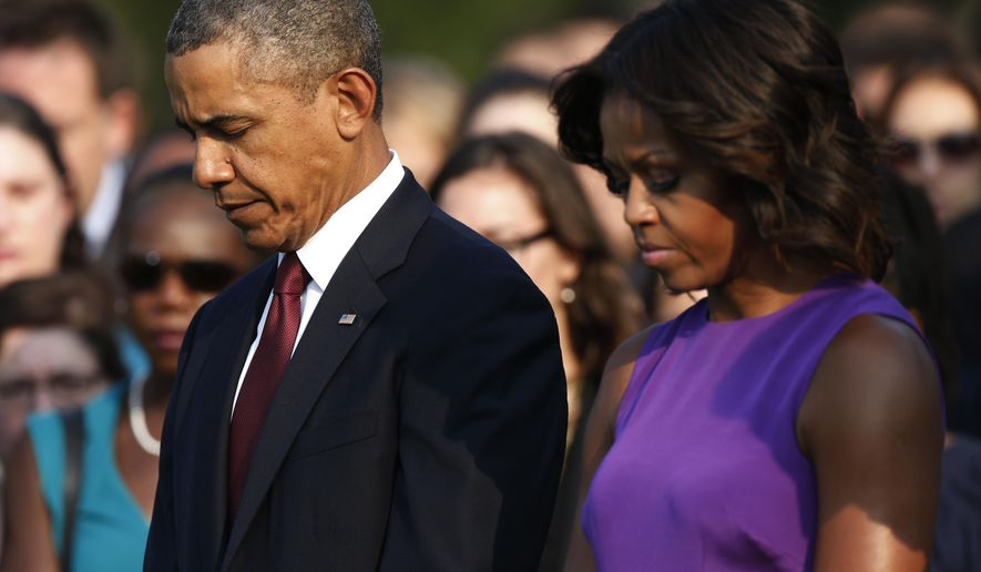 FILE - In this  Sept. 11, 2013, file photo, President Barack Obama and first lady Michelle Obama stand for a moment of silence on the South Lawn at the White House in Washington, as they mark the 12th anniversary of the September 11 terror attacks. Five times, Obama has come before the American people to reckon with the legacy of the 9/11 terrorist attacks on the anniversary of that awful day. Each time, he has tailored his message to the moment, at different points stressing themes of service, resilience, tolerance, reconciliation.  (AP Photo/Charles Dharapak, File)