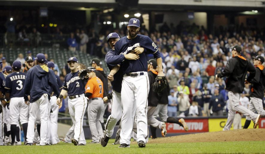 Milwaukee Brewers pitching coach Rick Kranitz restrains starting pitcher Mike Fiers as both benches rush the field during the fifth inning of a baseball game against the Miami Marlins Thursday, Sept. 11, 2014, in Milwaukee. (AP Photo/Morry Gash)