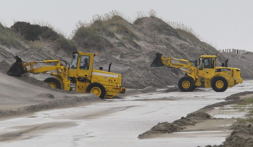 FILE - In this Sept. 3, 2010, file photo, Department of Transportation workers remove water and sand from a section of N.C. 12 on Pea Island near Nags Head, N.C., after winds from Hurricane Earl left the highway impassable. The state Transportation is delaying construction of a bridge at Pea Island until the court case involving the longer span to the north, the Bonner Bridge, is settled. (AP Photo/Gerry Broome, File)