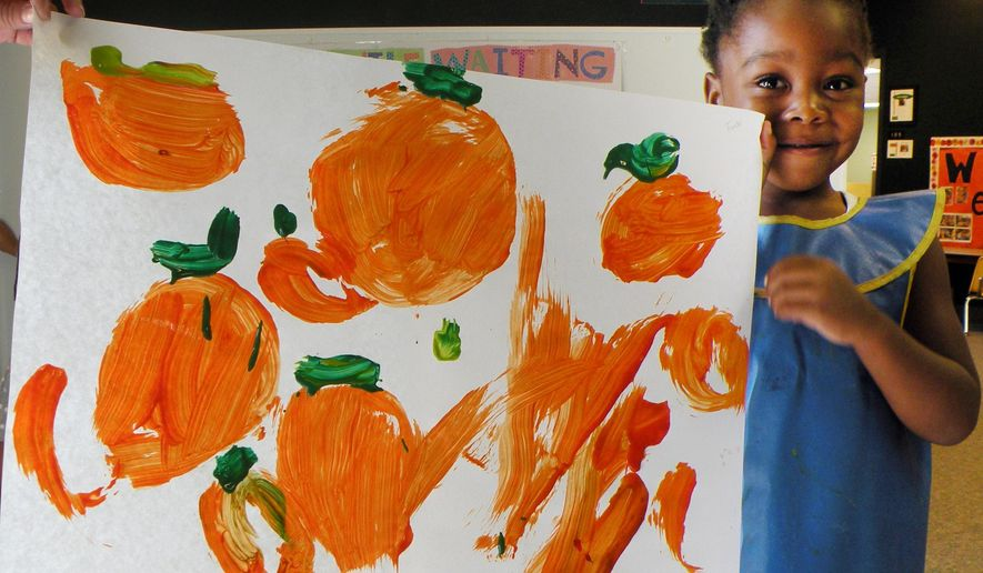 In this photo taken on Sept 9, 2014, and provided by the Child Development Center, student Oluwafunto Akinnurele holds a picture of pumpkins stolen from the Child Development Center at Eastern New Mexico University in Portales, N.M. Officials say the pumpkin patch was raided sometime over the weekend after students had worked for months growing the pumpkins. (AP Photo/Child Development Center)