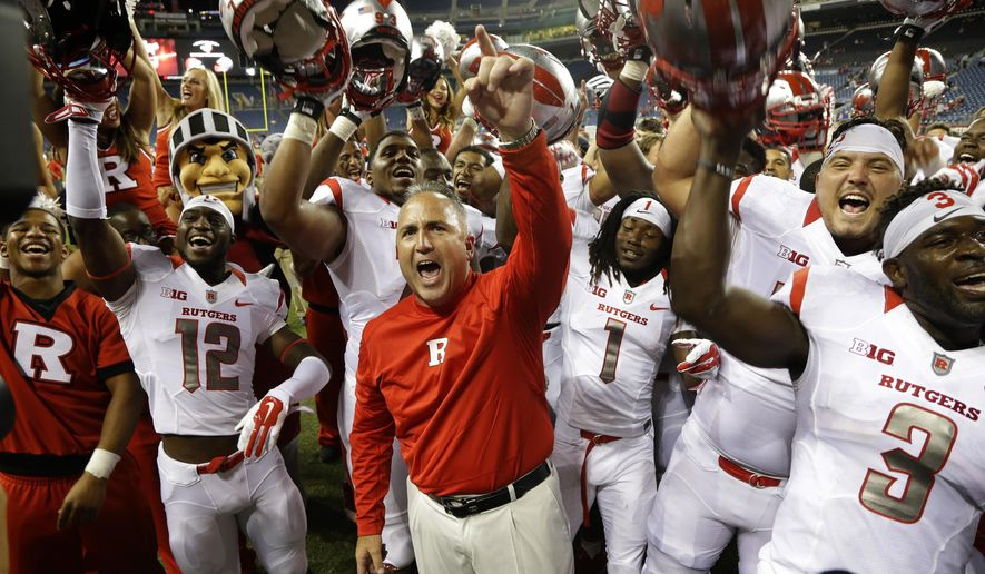 FILE - In this Aug. 28, 2014, file photo, Rutgers head coach Kyle Flood, center, celebrates with his team after they beat Washington State 41-38 in an NCAA college football game in Seattle. Rutgers has given Flood a two-year contract extension. Athletic Director Julie Hermann announced the deal Thursday, Sept. 11, 2014, two days before the Scarlet Knights (2-0) play their first Big Ten Conference game against Penn State (2-0).  (AP Photo/Ted S. Warren, File)