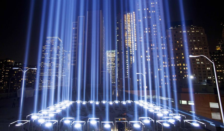 FILE- In this Sept. 10, 2013 file photo, the Tribute in Light rises above buildings during a test in New York. While the plaza at the National September 11 Memorial and Museum will be closed to the public, during the September 11 commemoration ceremony and much of the rest of the day, it will be open from 6 p.m. to midnight for those who want to pay respects and view one of the anniversary's most evocative traditions, the twin beams called the Tribute in Light. (AP Photo/Mark Lennihan, File)