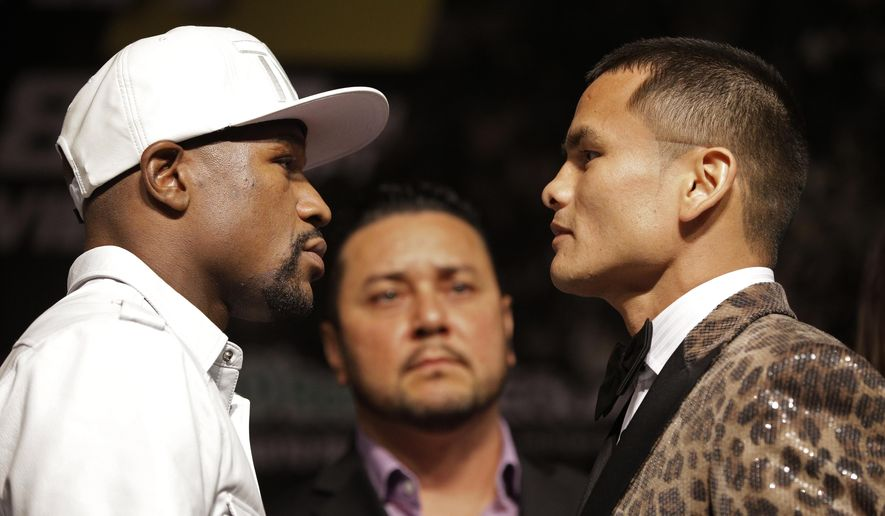 Boxers Floyd Mayweather Jr., left, and Marcos Maidana pose during a press conference Wednesday, Sept. 10, 2014, in Las Vegas. The two are scheduled to fight in a welterweight title fight Saturday in Las Vegas. (AP Photo/John Locher)
